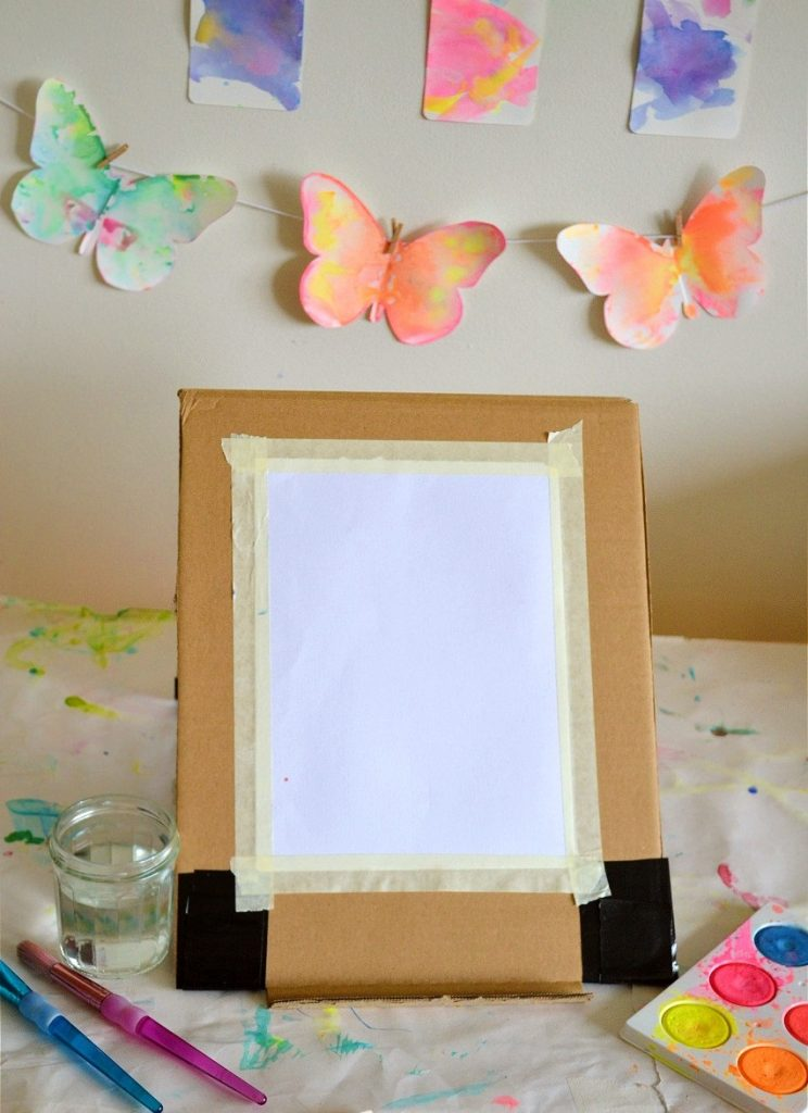 front view cardboard easel with paint palette and paintbrushes