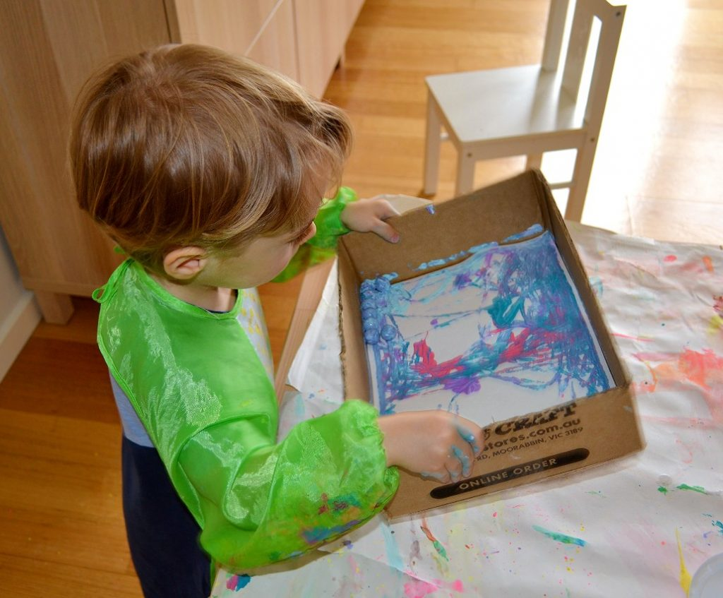 Toddler holding box with paint and marbles