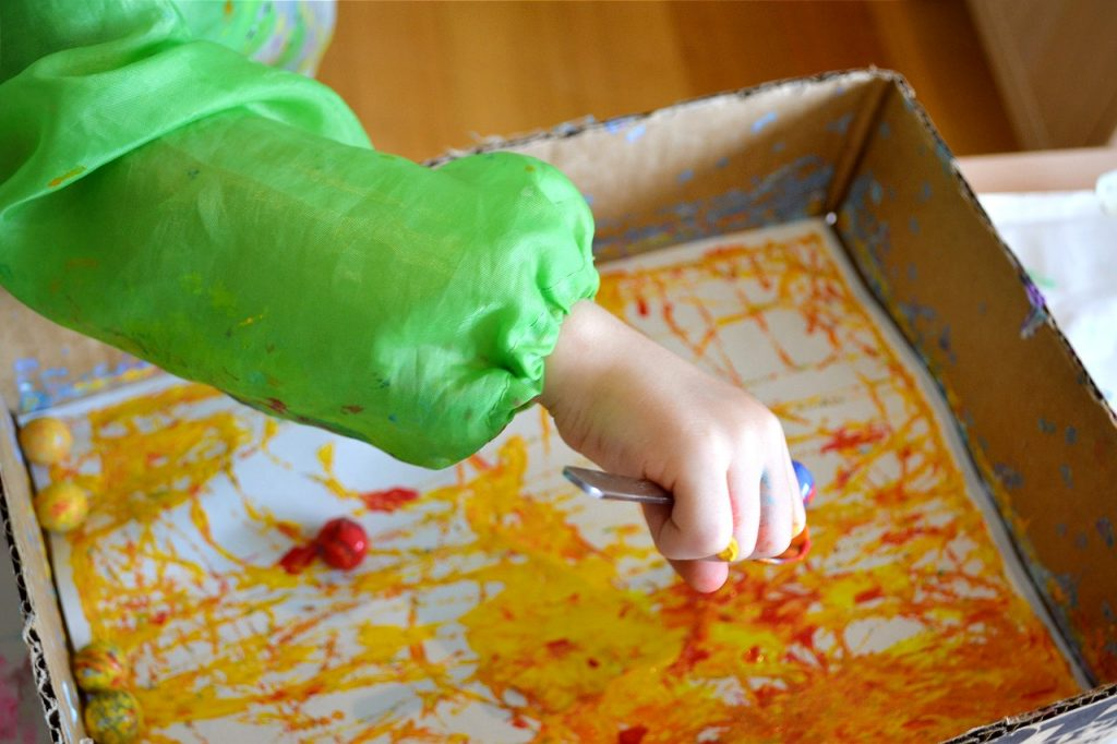 toddler hand holding spoon with paint and marbles over box