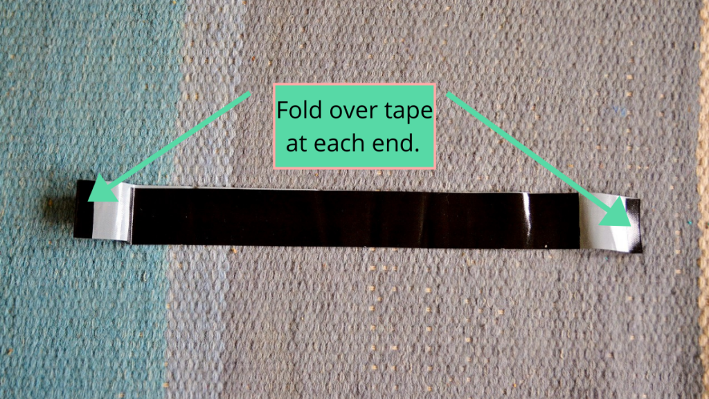Cardboard easel project directions with arrows indicating where to fold duct tape