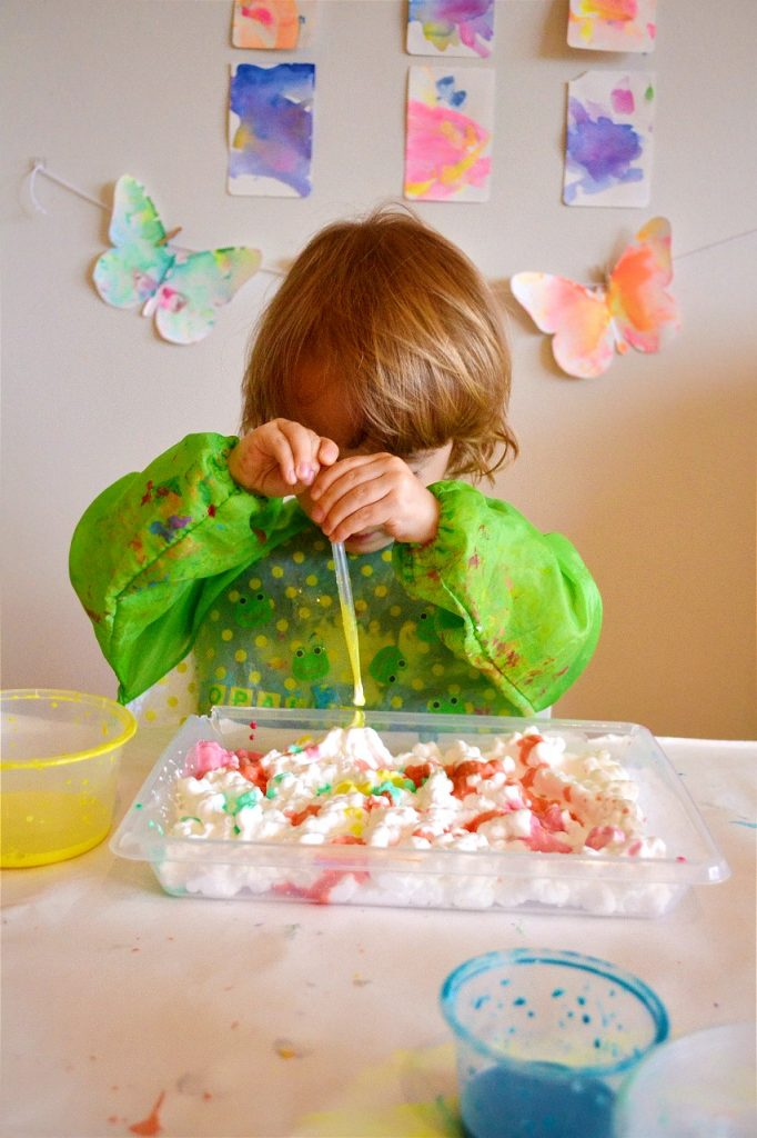 Toddler squeezing pipette into tray of shaving cream