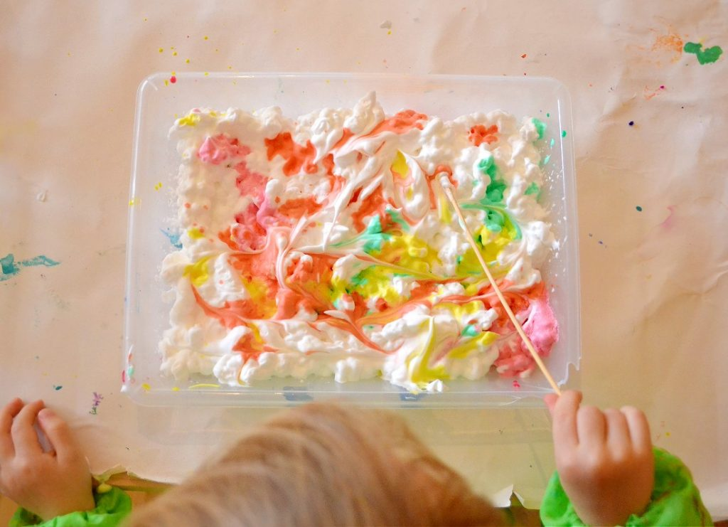 toddlers swirling shaving cream and paint with stick