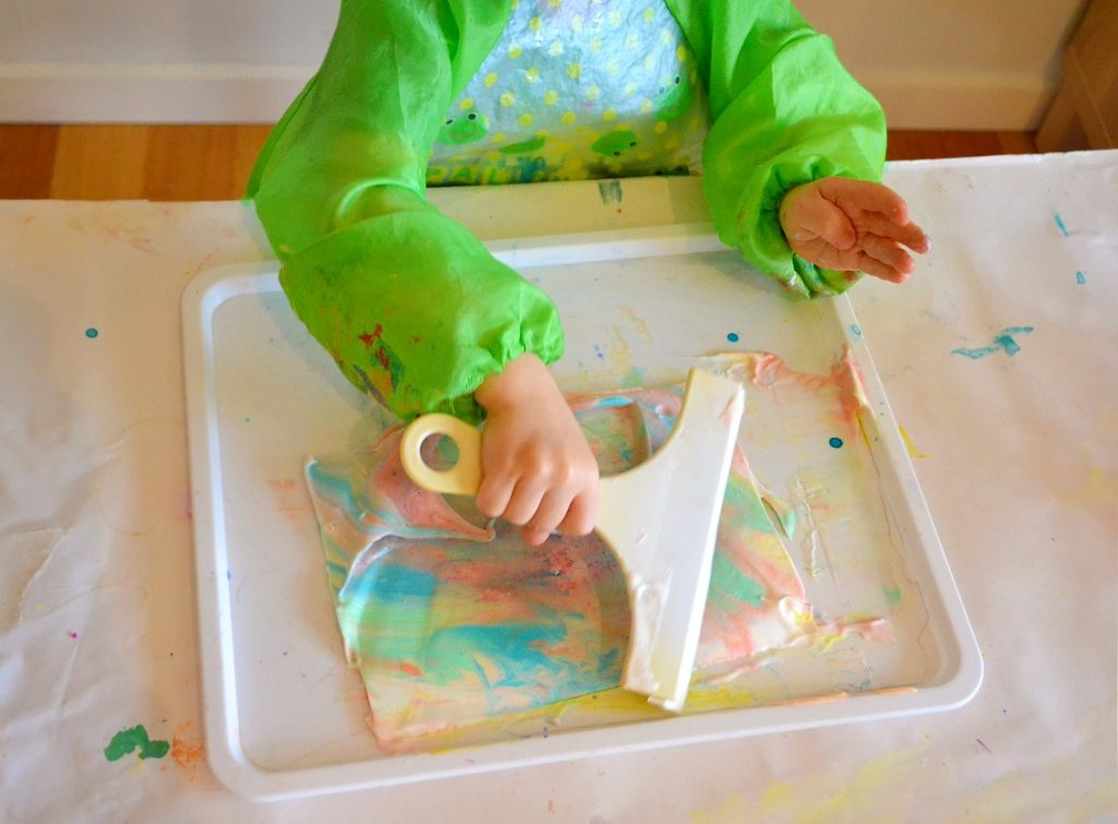 toddler hand scraping shaving cream off paper with squeegee