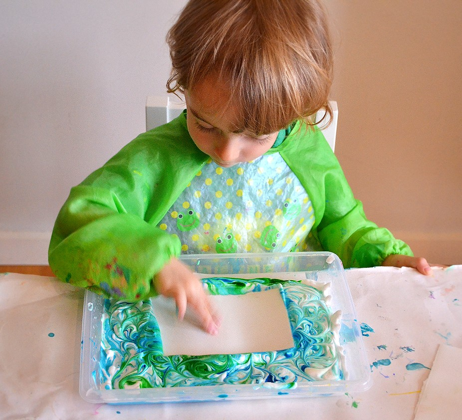 Toddler tapping paper into tray with shaving cream and paint